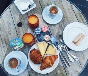 table de brunch avec viennoiseries fromages café jus de fruits