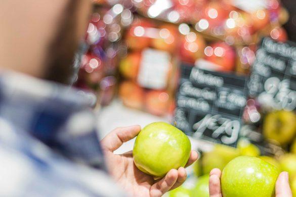Un homme choisit des pommes dans un supermarché