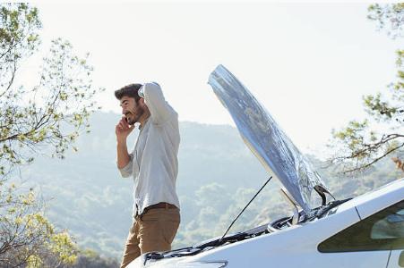 homme au téléphone devant voiture en panne avec capot relevé