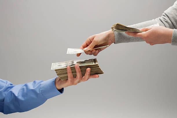 Deux personnes qui s'échangent des billets pour verser un salaire