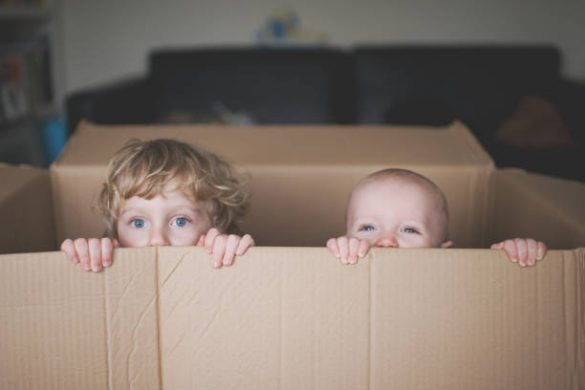 Deux enfants qui se cachent dans un carton de déménagement
