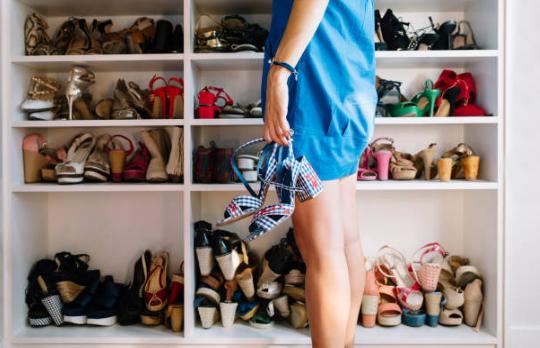 femme se tenant devant un placard rempli de chaussures et portant une paire de chaussures à la main