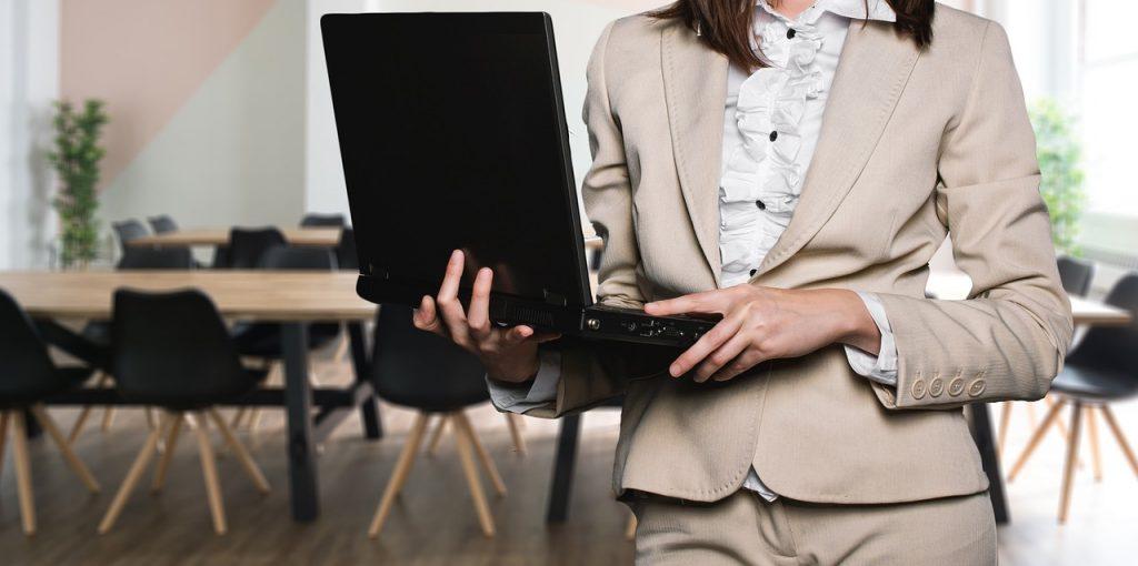 vue d'une femme de buste en tailleur beige avec un ordinateur portable