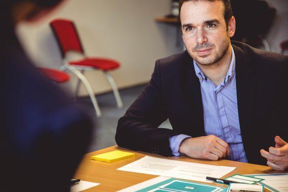 homme portant une veste de costume noir et une chemise bleu assis à une table avec des papiers