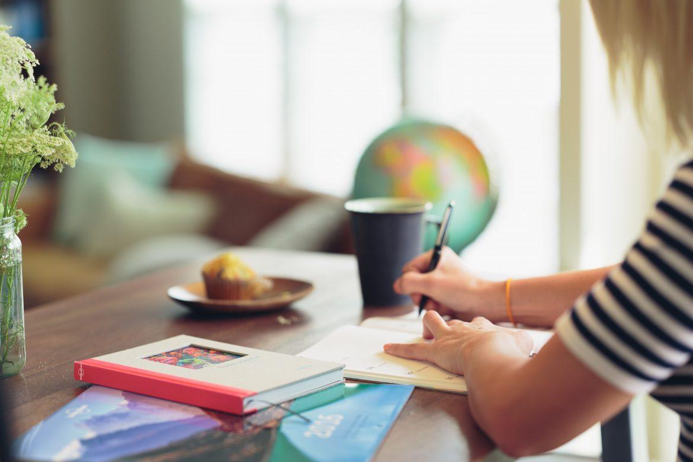 Jeune étudiante assise à une table qui écrit sur un carnet