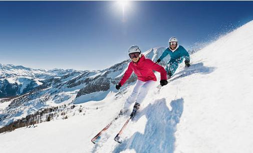 deux personnes qui skient face aux montagness