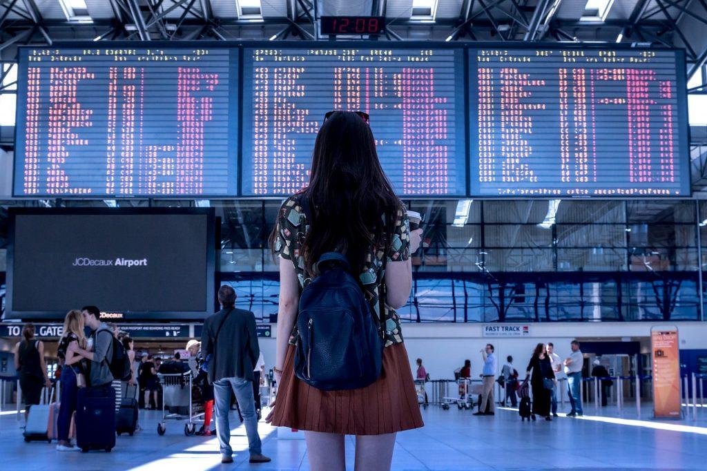 femme se tenant devant le tableau des vols dans un aéroport