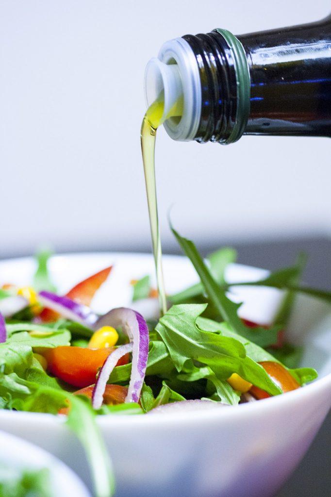 Bol de salade sur lequel de l'huile est versé