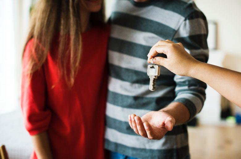 personne remettant des clés à deux autres personnes