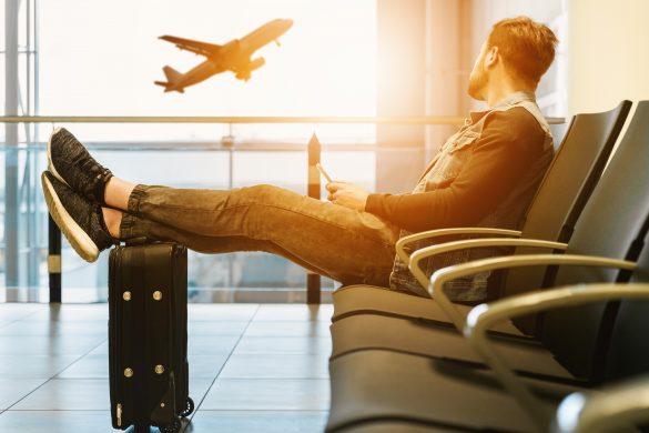homme assis dans un aéroport avec les pieds sur sa valise regardant les avions décoller