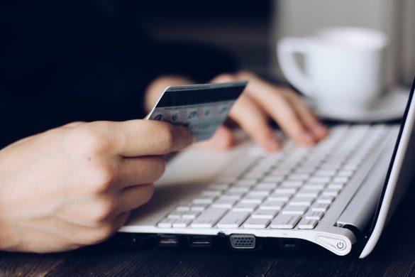 personne tenant une carte de credit dans une main et tapant à l'ordinateur de l'autre