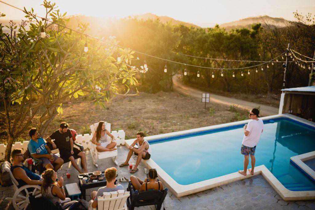 groupe d'amis prenant l'apéritif près d'une piscine dans un extérieur avec guirlande lumineuse