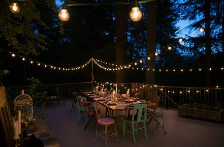 terrasse en soirée avec table et chaises et guirlande lumineuse