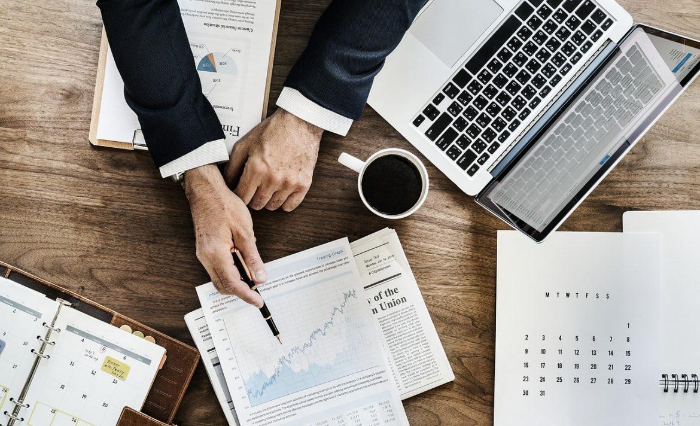 vue de dessus d'un bureau avec une personne qui montre des documents avec ordinateur portable agenda et tasse de café posés à côté